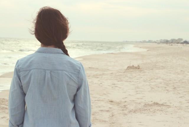 Una ragazza guarda il mare e le onde pensando all'amica da perdonare